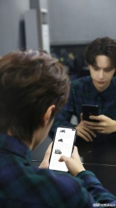 A candid photo of Wang Yibo holding the Redmi K30
